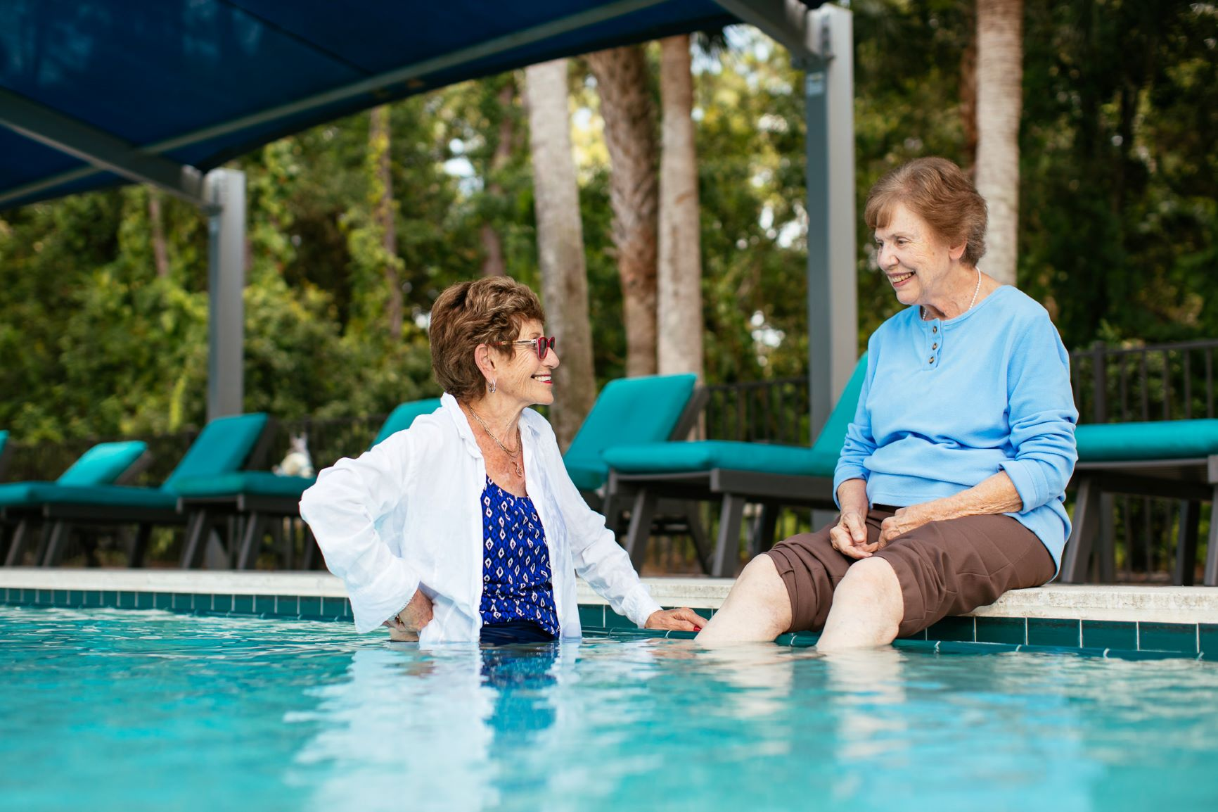 Aviva Senior Living swimming pool with two women talking.