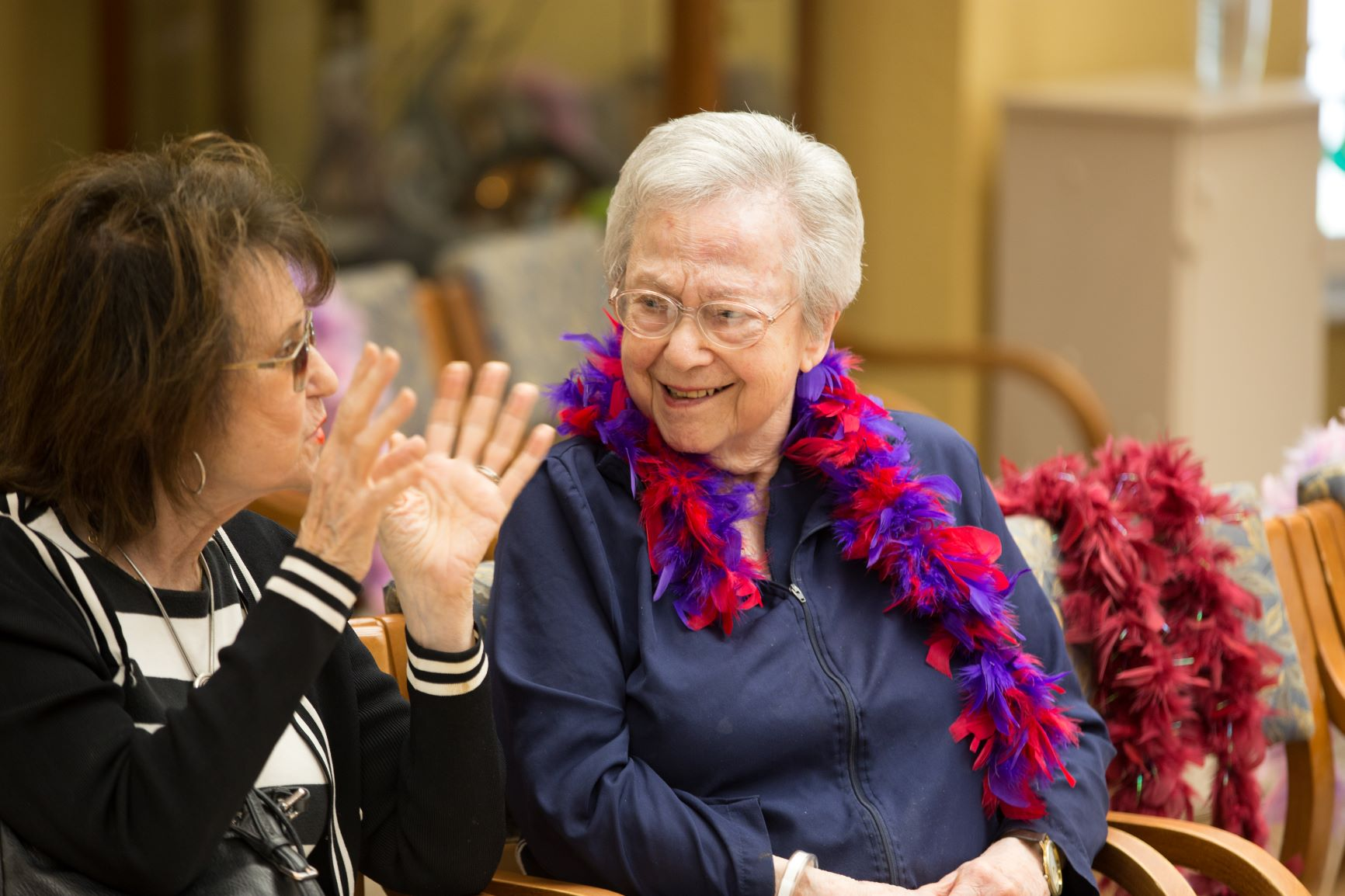 Two female senior assisted living residents having a conversation.