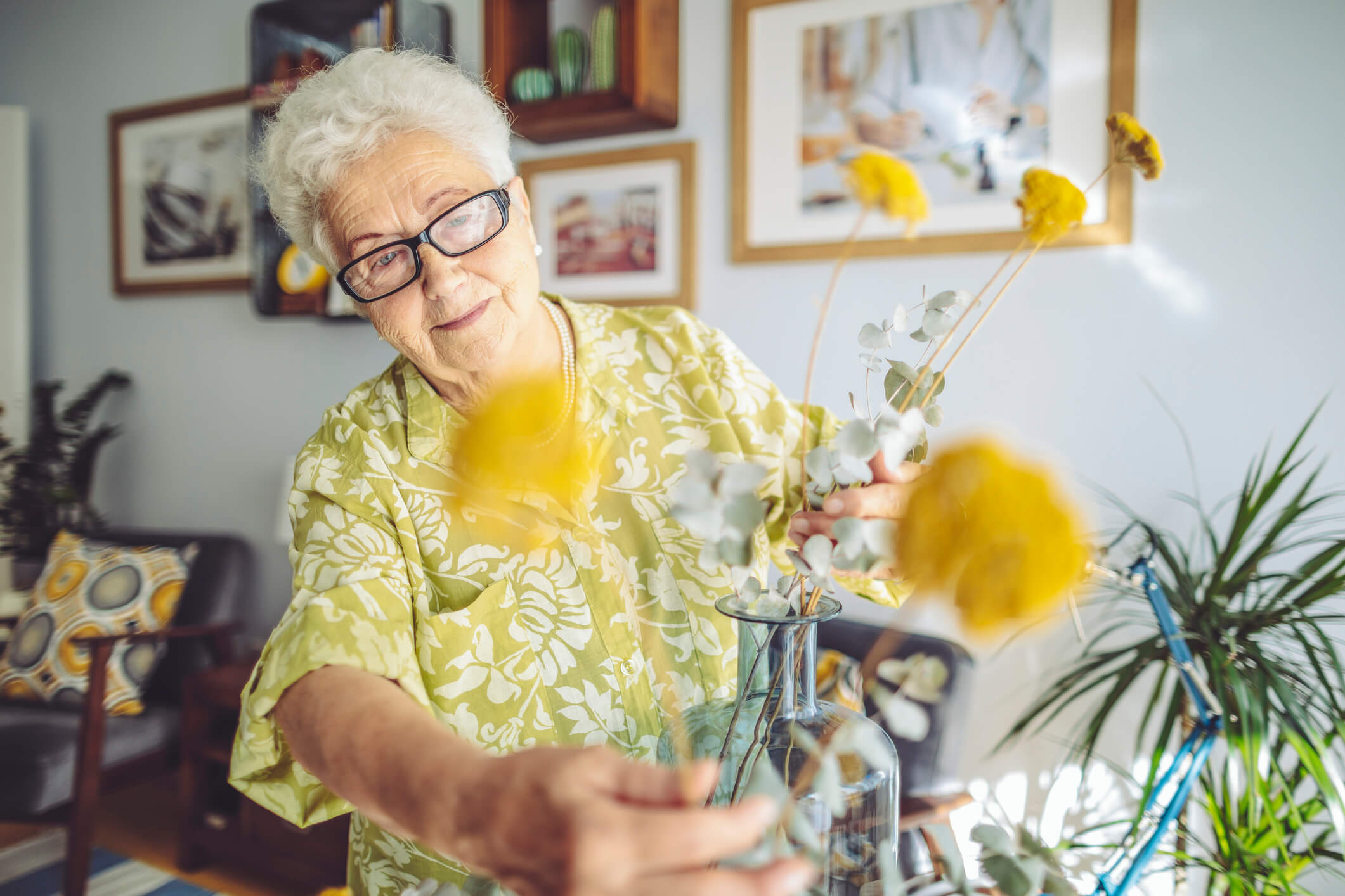 Senior woman decorating flowers in her home.