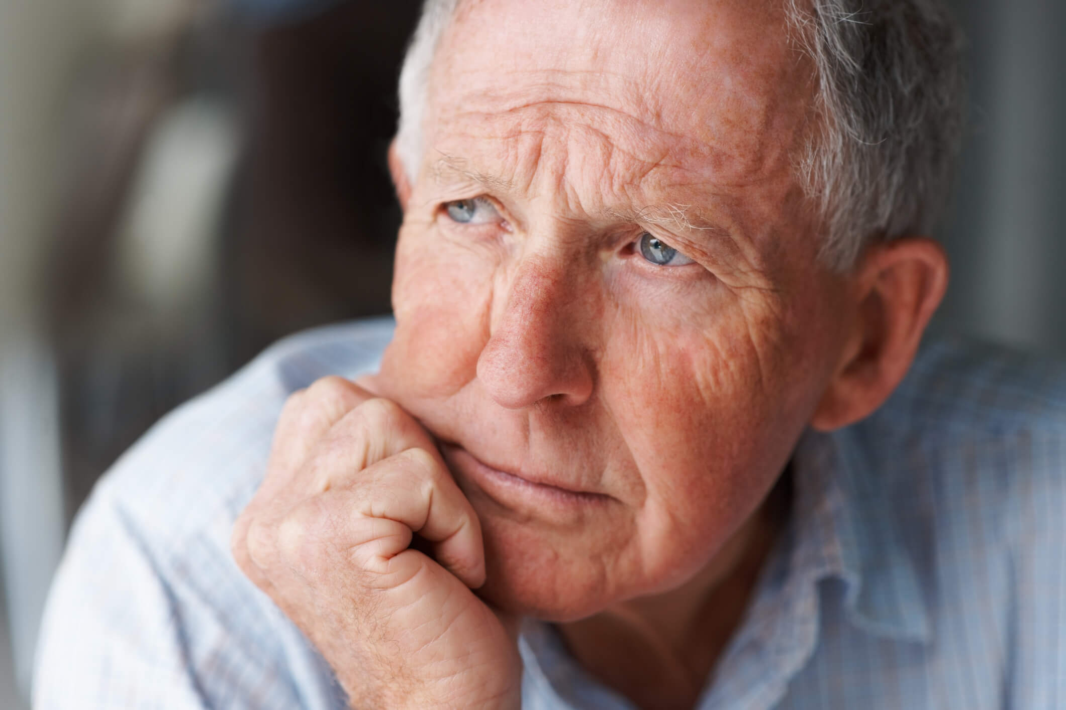 Senior man with depression sitting with his face on his fist.
