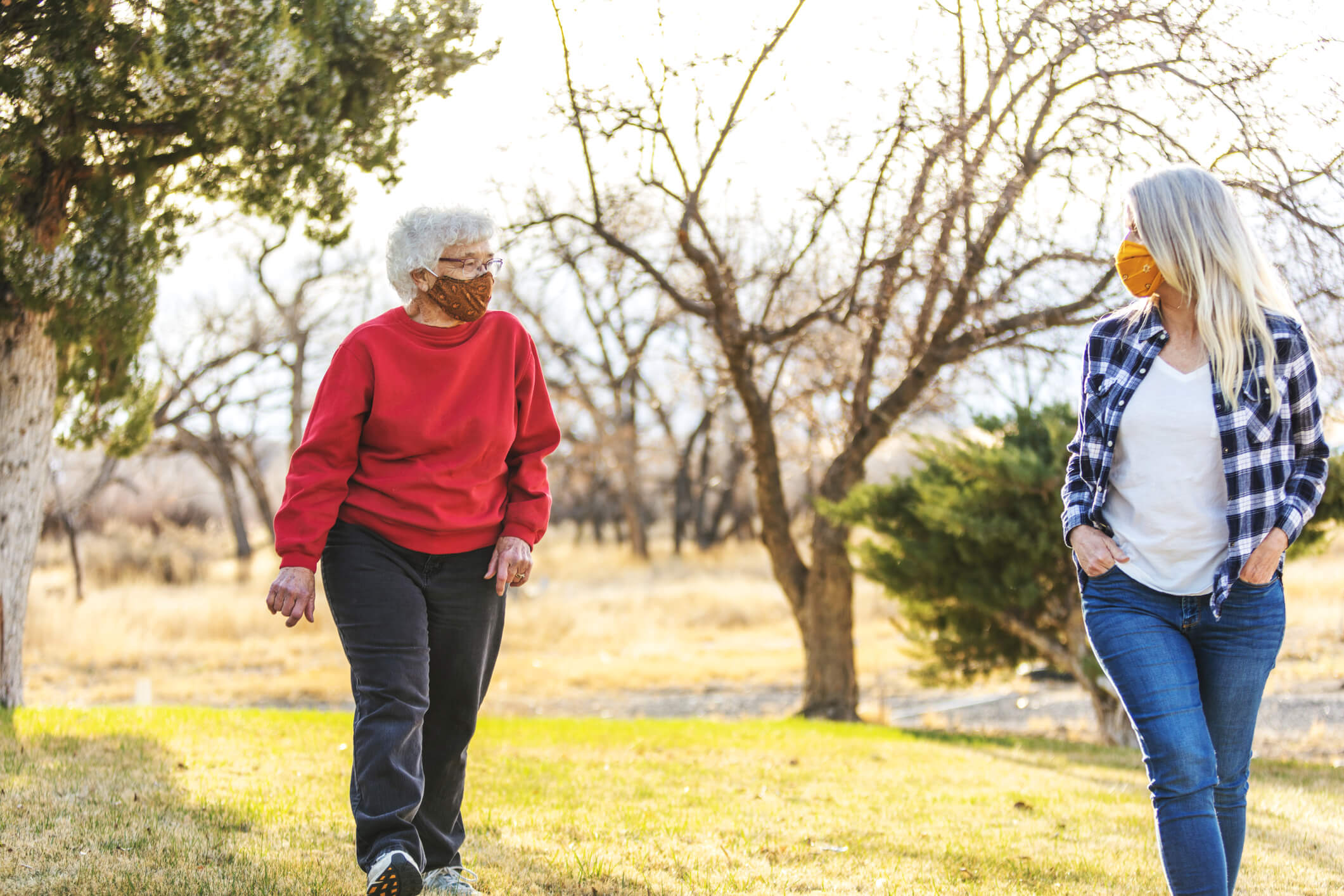 Senior mother and adult daughter walking outdoors and social distancing while wearing masks.
