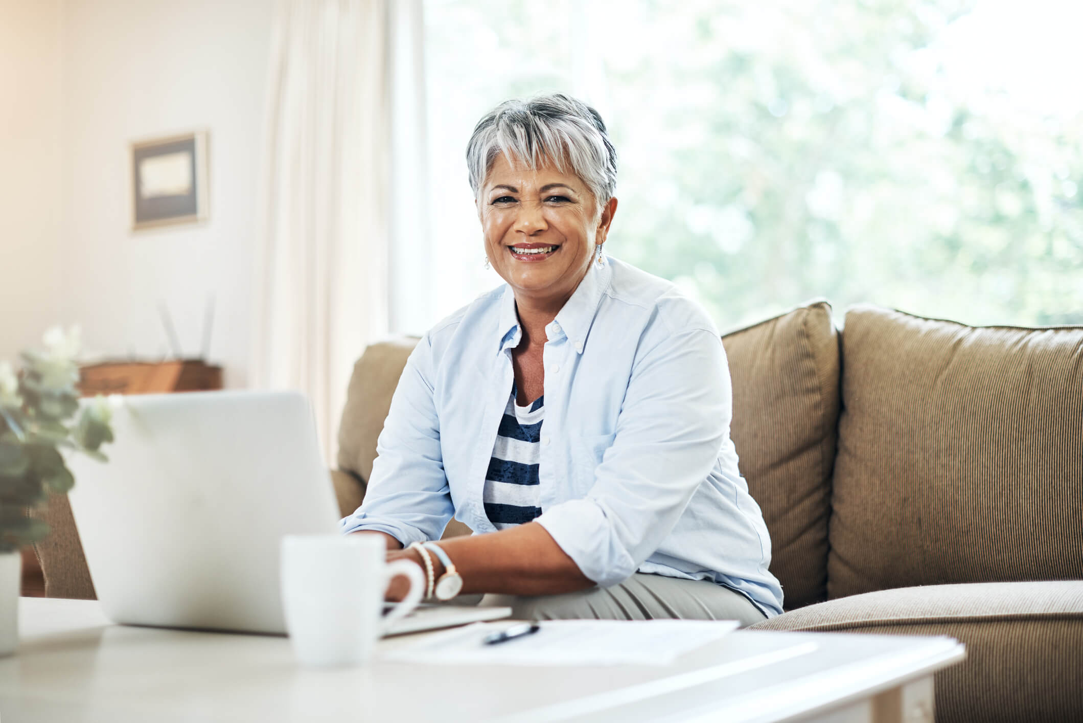 Senior woman planning a budget for her retirement in her living room on a laptop.