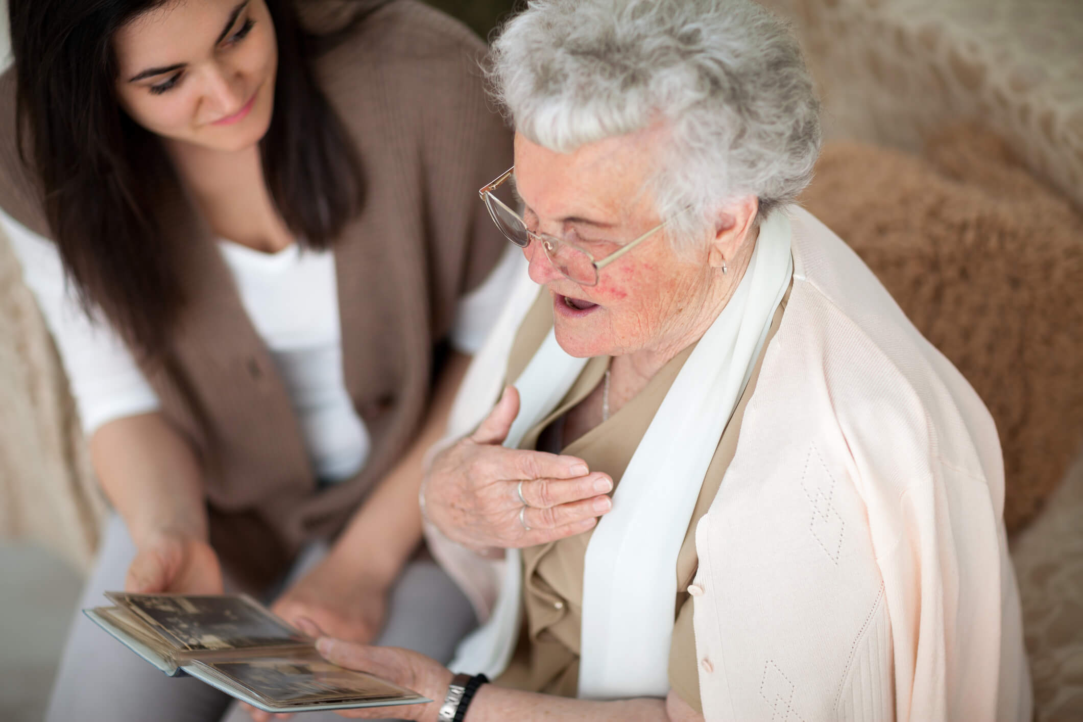 A senior with memory care needs looking at photos with a family member.