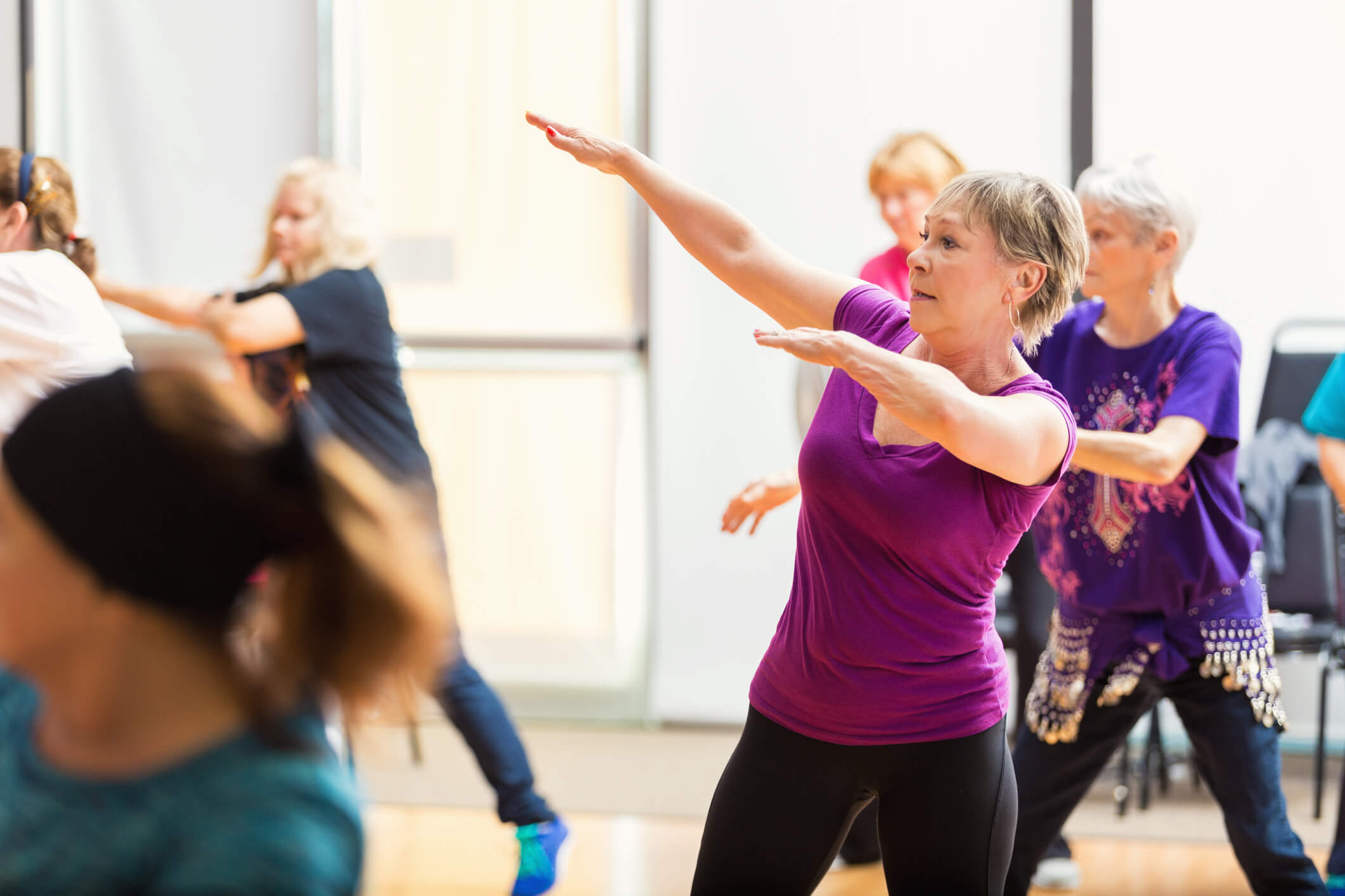 Senior woman posing in an aerobic group dance class.