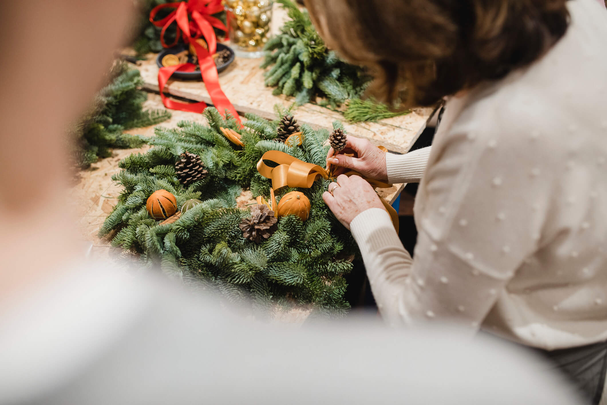 Closeup of a senior woman creating a holiday wreath.