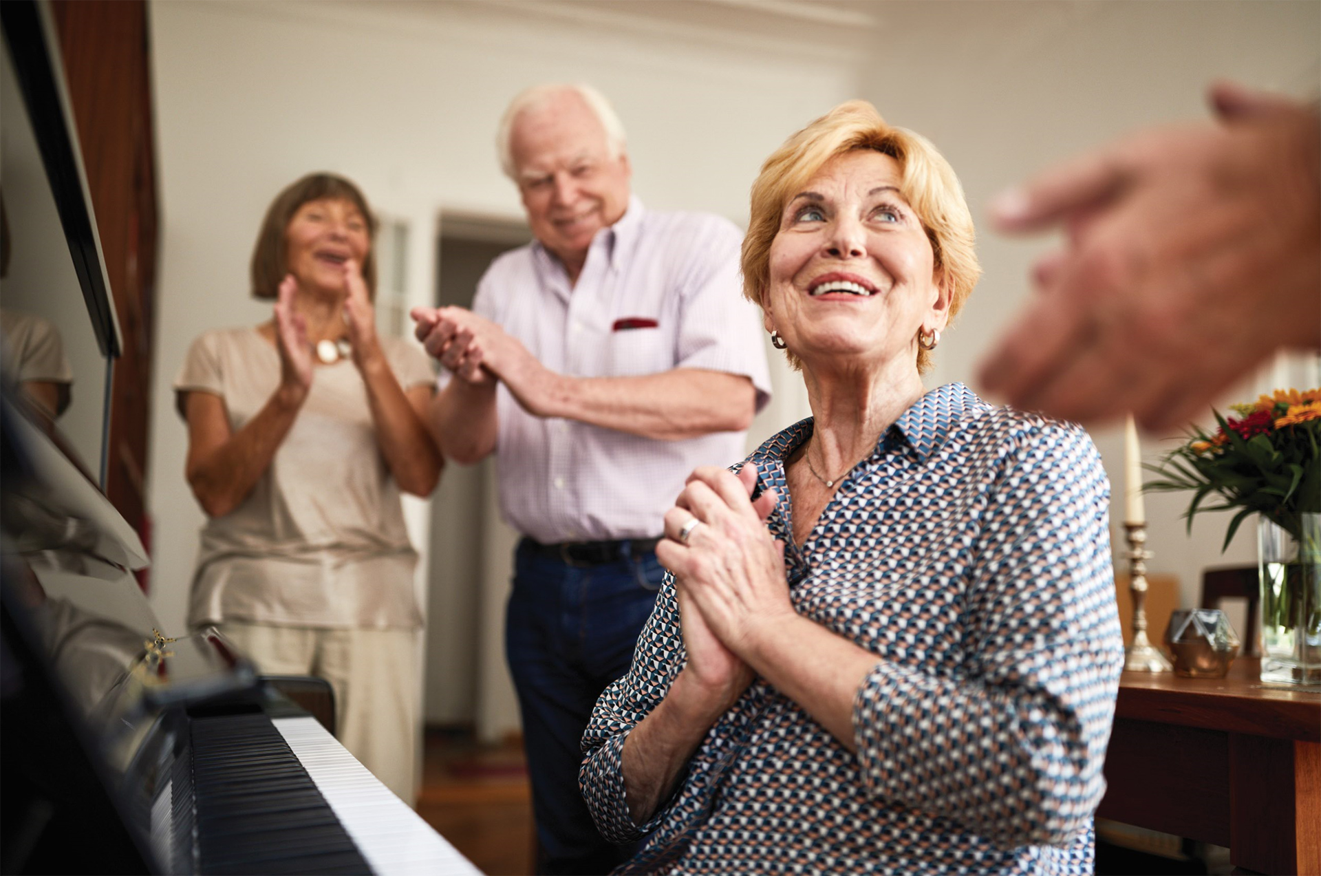 A female Aviva resident smiles with her hands clasped as other residenrs applaud her piano playing